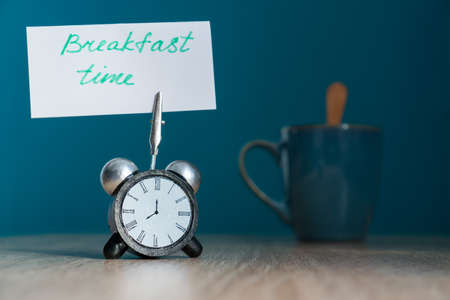 """Alarm clock and banner with handwritten phrase """"breakfast time"""" on wooden table. Time management concept."""