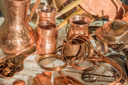 Vintage copper kitchenware and accessories - coffee pots, jars, rings, bracelets in flea market Archivio Fotografico