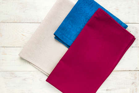Top view of cloth napkins of beige, blue and burgundy colors on rustic white background. 写真素材