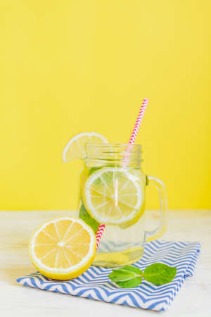 Citrus lemonade water with sliced lemon and mint, healthy and detox water drink in summer on yellow background. Summer bright backdrop with copy space
