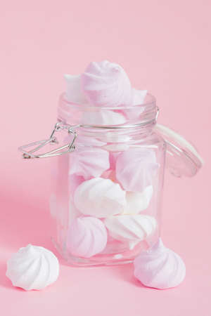 White and pink twisted meringues in a glass jar on pink background. French dessert prepared from whipped with sugar and baked egg whites.