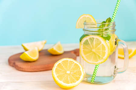 Mason jar glass of homemade lemonade with lemons, mint and green paper straw on wooden rustic table and blue background. Summer refreshing beverage.