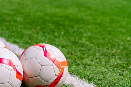 Football balls on a pich. Soccer background with copy space