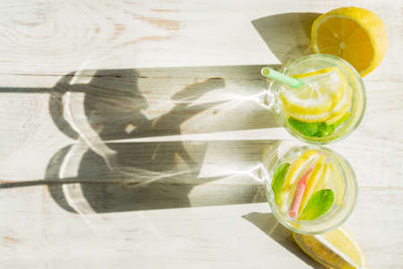 top view of glass of homemade lemonade with lemons, mint and paper straws on wooden rustic background. Summer refreshing beverage. hard shadows Zdjęcie Seryjne