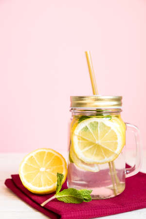 Citrus lemonade water with sliced lemon and mint, healthy and detox water drink in summer on wooden table with pastel pink background Zdjęcie Seryjne