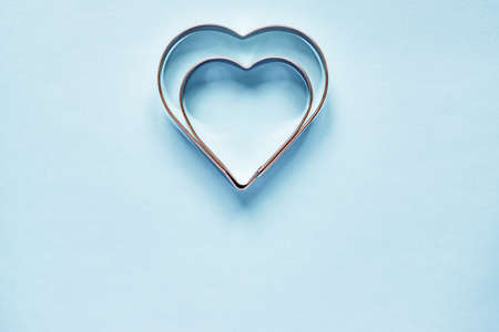 Two metal cookie cutters in heart shape on light blue background with copy space