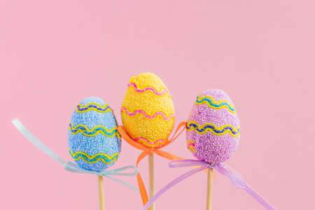 Easter purple, yellow and blue decorated eggs stand on a wooden sticks on pink background. Minimal easter concept. Happy Easter card with copy space for text.