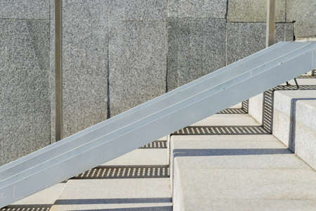 tiled stairs and steel railing ramp for wheelchair, carts and strollers with granite wall and hard sun shadows. Abstract city background