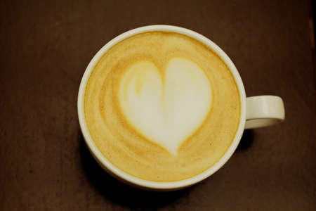top viewof big cup of freshly brewed cappuccino with soft foam and heart on wooden table.