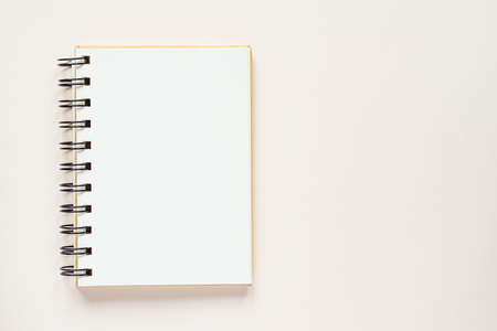Clean spiral note book for notes and messages on rlight beige background. Minimal business flat lay