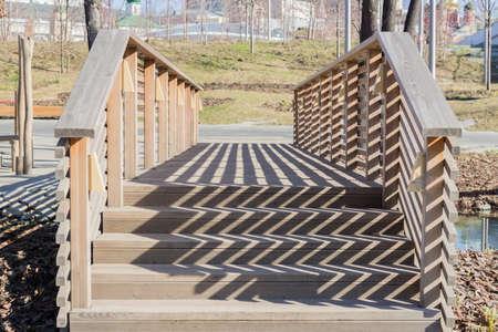 Wooden bridge in the park and Railing hard Shadows Фото со стока