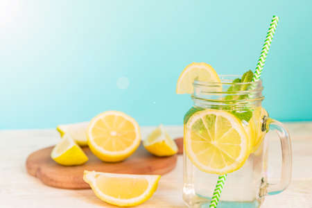 Mason jar glass of homemade lemonade with lemons, mint and green paper straw on wooden rustic background. Summer refreshing beverage.