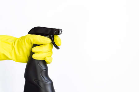 hand in pink rubber glove holding black plastic spray detergent bottle. Household chemicals. Cleaning product.