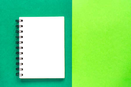 Clean spiral note book for notes on green background. Minimal business flat lay mock up