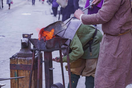 Blacksmith workshop on the street. People in traditional clothses forge metal