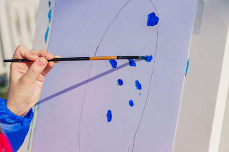 Artist's work place. A child paints with blue gouache a picture. Open air workshop Imagens