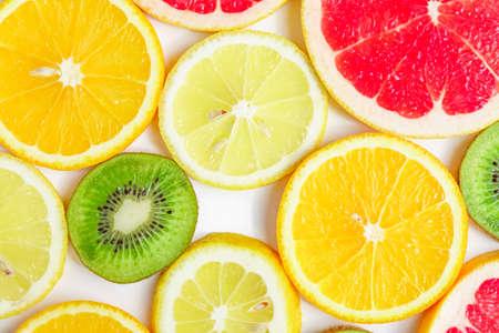 citrus slices - kiwi, oranges and grapefruits on white background. Fruits backdrop