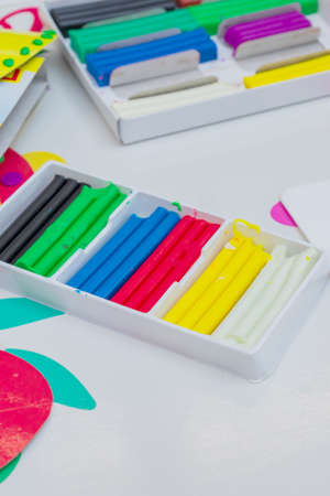 Set of colorful modeling clay in white paper box on a table