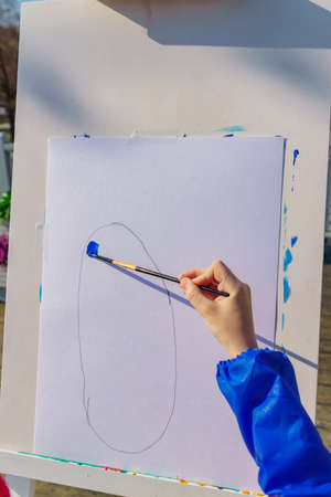 Artist's work place. A kid paints with blue gouache a picture. Open air workshop