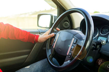 Man in red sweatshirt driving a car in a sunny day. traveling concept.
