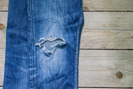 top view of blue faded jeans with a hole on wooden background. Beauty, fashion and shopping concept. Copy space for text Stock fotó