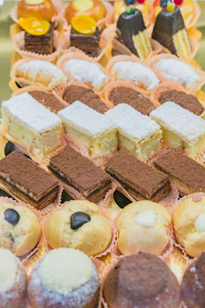 Pastry shop display window with variety of mini desserts and cakes, candy bar, selective focus
