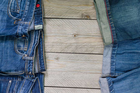 top view of blue denim jeans arranged on wooden background. Beauty and fashion clothing concept Stock fotó