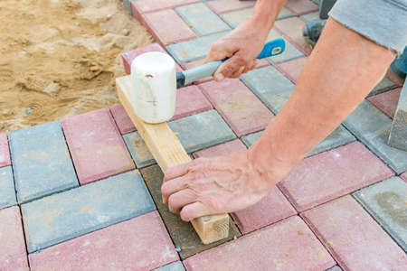 Worker laying red and gray concrete paving blocks. Road Paving, construction. Stock Photo