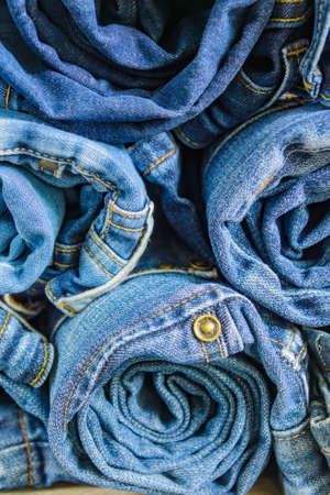 roll blue denim jeans arranged in stack, background texture. Beauty and fashion clothing concept Stock fotó