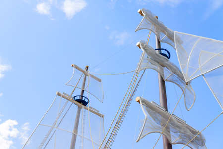 Sails of the boat against blue sky.