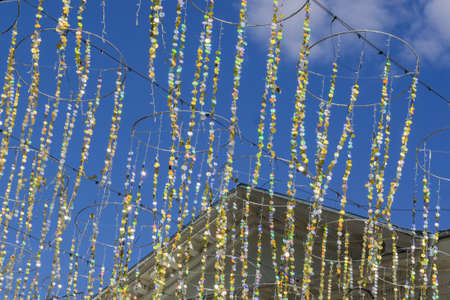 festive glitter ribbons with gold circles against building facade and blue sky. Colorful garland for city event decoration