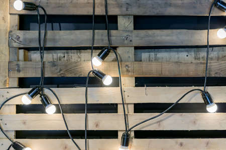 Loft style background. Garland with bulbs and wooden pallet on the wall