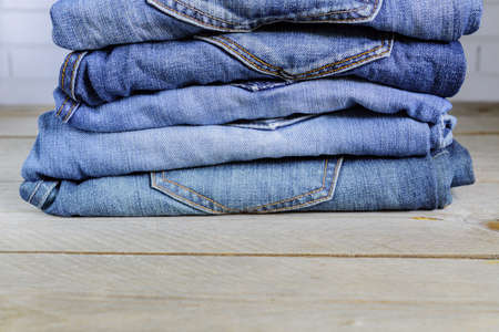 Stack of blue jeans on wooden shelf. Beauty and fashion clothing concept with copy space