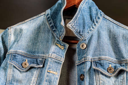 Blue denim woman jacket on a wooden hanger. Trendy clothes.