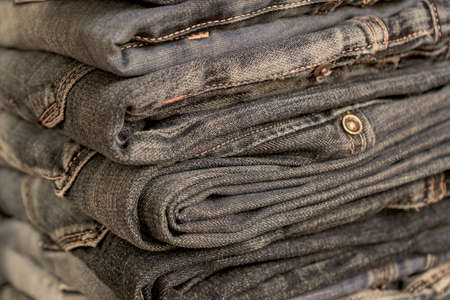 Stack of blue jeans on wooden shelf with copy space. Beauty and fashion clothing concept, selective focus