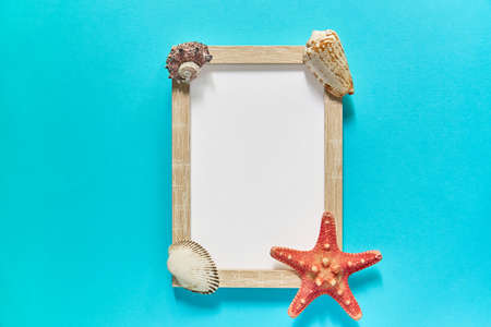 top view of photoframe with seashells and starfish on blue background. Summer vacation concept. Sea flat lay