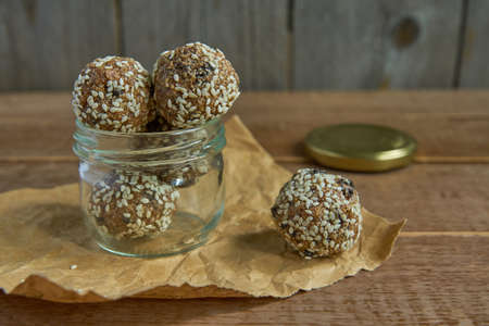 Tasty vegan raw protein truffles or energy balls with prunes, seeds and nuts in a jar on wooden background