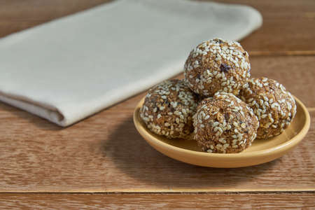 Oatsmeal sesame protein balls. Low fat energy bites with oatmeal, nuts sesame and prunes on wooden background