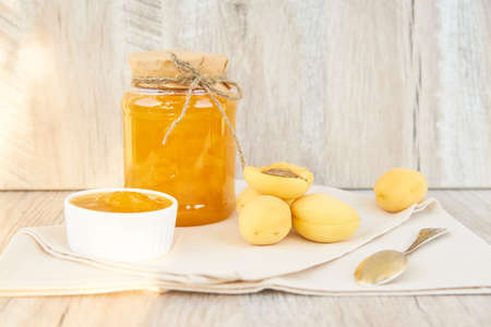 Home made organic apricot jam in glass jar and ripe apricots on wooden rustic table
