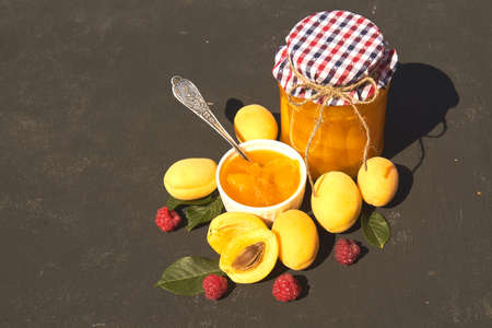 Top view of jar with homemade organic apricot jam and ripe apricots and raspberry on black background. Copy space for your text