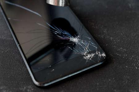 Smartphone with broken glass screen and hammer on dark background.