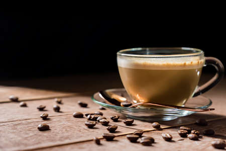 Cup of hot coffe with milk on a dark background. latte or cappuccino on a wooden table with copy space