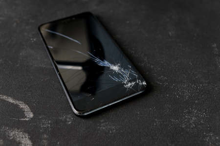 Broken mobile phone display with a big black iron hammer in the screen