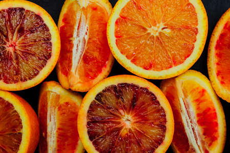 Top view of fresh blood orange halves and quaters. Fruit background