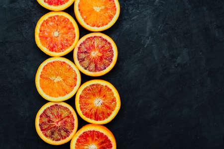 Sliced Sicilian blood oranges on black stone natural background, top view