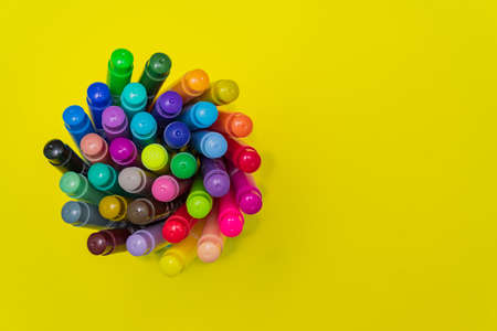 Set of felt tip pens rolled on a bright yellow background. Top view. Art and school creative concept with copy space Stockfoto