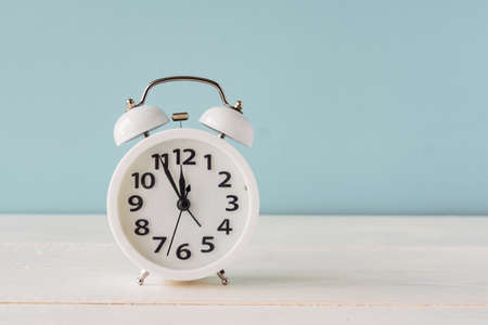White alarm clock standing on wooden shelf on blue background. copy space fro your text or design. Fime minutes before twelve on a display.