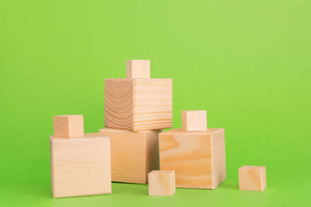Construction of wooden cubes on green background with copy space. Mockup composition for design.