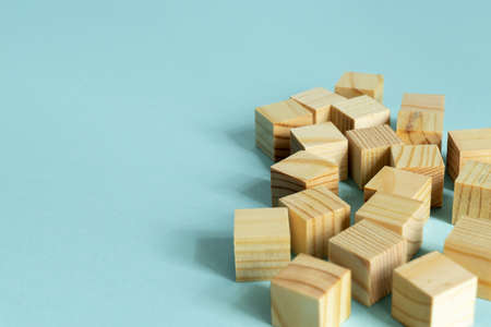 Construction of wooden cubes on blue background with copy space. Mockup composition for design.