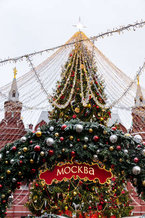 Christmas arch decorated with baubles and snow. Red signboard with word in Russian Moscow. Moscow Seasons Project.